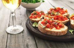 Bruschetta用蕃茄、山羊乳干酪和蓬蒿 库存照片