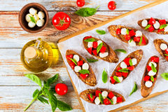 Bruschetta用蕃茄、微型无盐干酪和蓬蒿叶子 免版税库存图片