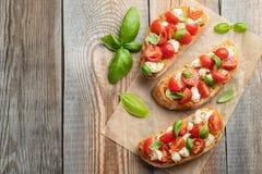 Bruschetta用蕃茄、无盐干酪乳酪和蓬蒿在一张老土气桌上 传统意大利开胃菜或快餐 免版税库存图片