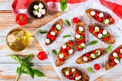 Bruschetta用蕃茄、无盐干酪和蓬蒿在黑麦baguett 库存照片