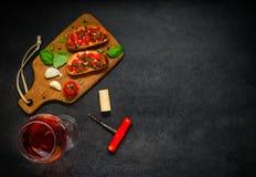 Bruschetta用蕃茄、蓬蒿和玫瑰酒红色在拷贝空间 免版税图库摄影