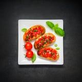 Bruschetta用蕃茄和蓬蒿在白色板材 免版税图库摄影