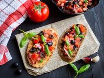 Bruschetta用蕃茄和蓬蒿在黑木板 库存图片