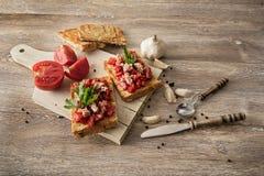 Bruschetta用蕃茄和金枪鱼在木背景 库存图片