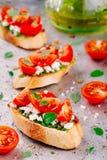 Bruschetta用pesto调味汁、希腊白软干酪、蕃茄和蓬蒿 免版税库存图片