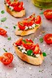 Bruschetta用pesto调味汁、希腊白软干酪、蕃茄和蓬蒿 库存照片