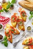 Bruschetta,烤切片长方形宝石用无盐干酪乳酪、蕃茄、大蒜和芳香蓬蒿在一张白色木桌上 图库摄影