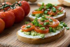 Bruschetta μαγειρέματος με το τυρί κρέμας, το αβοκάντο και τις τεμαχισμένες ντομάτες Στοκ Φωτογραφίες