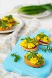 Bruschetta με τα ανακατωμένα αυγά και το arugula Στοκ Εικόνες