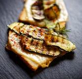 Bruschetta με τα ψημένα στη σχάρα κολοκύθια, το τυρί και τα χορτάρια στο μαύρο υπόβαθρο Στοκ φωτογραφία με δικαίωμα ελεύθερης χρήσης