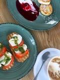 Bruschetta με τη μοτσαρέλα και το pesto, τηγανίτες cappuccino και τυριών με τη μαρμελάδα Στοκ εικόνες με δικαίωμα ελεύθερης χρήσης