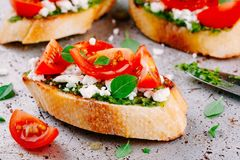 Bruschetta με τη σάλτσα pesto, το τυρί φέτας, τις ντομάτες και το βασιλικό Στοκ φωτογραφία με δικαίωμα ελεύθερης χρήσης