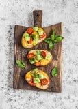 Bruschetta με τις ντομάτες και αβοκάντο στον αγροτικό ξύλινο τέμνοντα πίνακα εύγευστο πρόχειρο φαγητ στοκ εικόνα με δικαίωμα ελεύθερης χρήσης