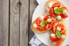 Bruschetta με τις ντομάτες και τη μοτσαρέλα κερασιών Στοκ Εικόνες