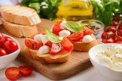 Bruschetta με τις ντομάτες κερασιών και μοτσαρέλα στον ξύλινο πίνακα Στοκ Εικόνες