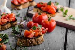 Bruschetta με τις ντομάτες, το σκόρδο και τα χορτάρια Στοκ Εικόνα