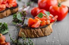 Bruschetta με τις ντομάτες, το σκόρδο και τα χορτάρια Στοκ Εικόνες