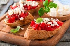 Bruschetta με τις ντομάτες, το τυρί φέτας και το βασιλικό Παραδοσιακό ελληνικό πρόχειρο φαγητό στο ξύλινο υπόβαθρο Στοκ Εικόνα