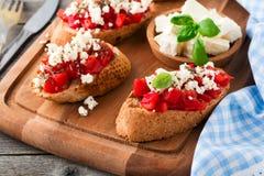 Bruschetta με τις ντομάτες, το τυρί φέτας και το βασιλικό Παραδοσιακό ελληνικό πρόχειρο φαγητό στο ξύλινο υπόβαθρο Στοκ φωτογραφία με δικαίωμα ελεύθερης χρήσης