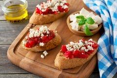 Bruschetta με τις ντομάτες, το τυρί φέτας και το βασιλικό Παραδοσιακό ελληνικό πρόχειρο φαγητό στο ξύλινο υπόβαθρο Στοκ Φωτογραφίες