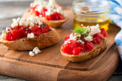 Bruschetta με τις ντομάτες, το τυρί φέτας και το βασιλικό Παραδοσιακό ελληνικό πρόχειρο φαγητό στο ξύλινο υπόβαθρο Στοκ Εικόνες