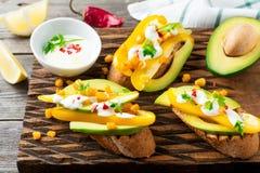 Bruschetta με το αβοκάντο, κίτρινο πιπέρι, σιτάρια του πιπεριού καλαμποκιού, μαϊντανού και τσίλι σε ένα ελαφρύ ξύλινο υπόβαθρο Στοκ εικόνες με δικαίωμα ελεύθερης χρήσης