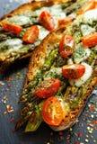 Bruschetta με το ψημένο στη σχάρα πράσινο σπαράγγι, τυρί μοτσαρελών και ντομάτα κερασιών Στοκ εικόνα με δικαίωμα ελεύθερης χρήσης