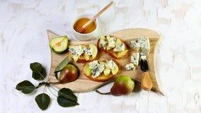 Bruschetta закуски с грушей, медом, грецким орехом и творогом на светлой деревянной доске, на светлой белой предпосылке Стоковые Фото