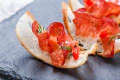Bruschetta закуски с отрывистой ветчиной на тонко отрезанном хлебе ciabatta на каменном конце предпосылки шифера вверх Стоковые Изображения RF