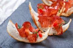 Bruschetta закуски с отрывистой ветчиной на тонко отрезанном хлебе ciabatta на каменном конце предпосылки шифера вверх Стоковые Фотографии RF