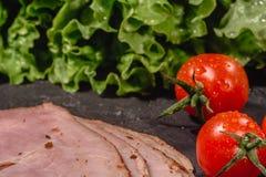 Ингредиенты для варить итальянское bruschetta на темной таблице Итальянское bruschetta с томатами вишни, соус сыра, листья салата стоковое фото