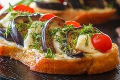 Bruschetta с зажаренными баклажанами, свежими томатами и сыром на черной плите Стоковые Изображения RF