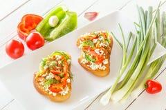 2 Bruschetta с красными сладостным перцем и козий сыром в плите рядом с свежими овощами Стоковое Изображение RF