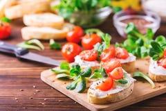 Bruschetta с рикоттой, шпинатом, салатом мозоли и томатами вишни Стоковые Фото