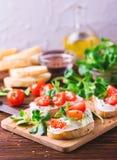 Bruschetta с рикоттой, шпинатом, салатом мозоли и томатами вишни Стоковая Фотография