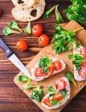 Bruschetta с рикоттой, шпинатом, салатом мозоли и томатами вишни Стоковые Изображения