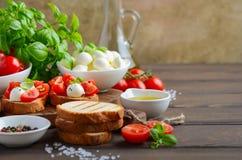 Bruschetta с томатами вишни и моццареллой на деревенской деревянной предпосылке Стоковые Изображения