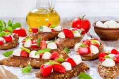 Bruschetta с томатами, моццареллой и базиликом, ингридиентами дальше Стоковое фото RF