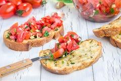 Bruschetta с томатами, травами и маслом на хлебе сыра чеснока Стоковое Фото