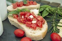 Bruschetta хлеба чеснока с томатами и ингридиентами вишни Стоковые Изображения