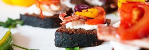 Το Bruschetta του μαύρου ψωμιού με τα φασόλια, τυρί, έψησε τα λαχανικά, τα πιπέρια και τις ντομάτες και το κρέας στη σχάρα στοκ φωτογραφία με δικαίωμα ελεύθερης χρήσης