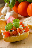 Bruschetta. With fresh ciabatta rolls, topped with tomatoes, feta and basil. Ingredients are visible in the background stock photo