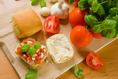Bruschetta. With fresh ciabatta rolls, topped with tomatoes, feta and basil. Ingredients are located next to the rolls stock photo