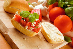 Bruschetta. With fresh ciabatta rolls, topped with tomatoes, feta and basil. Ingredients are visible in the background royalty free stock photos