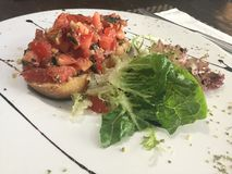 Bruschetta with green lettuce and balsamic vinaigrette. Bruschetta is an antipasto & x28;starter dish& x29; from Italy consisting of grilled bread rubbed with Royalty Free Stock Images
