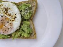 Bruschetta appetitosa con l'uovo e l'avocado su un piatto immagine stock libera da diritti