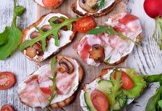 Bruschetta asortyment z kremowym serem, szampinionami, pancetta mi?sem, warzywami i greenery, zdjęcia stock
