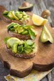 Bruschetta with avocado, arugula, lemon and pine nuts. On a wooden background stock photo