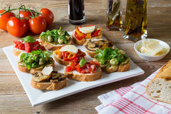 Bruschetta with beans and arugula, mushrooms, goat cheese. On a wooden board royalty free stock photo