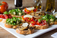Bruschetta with beans and arugula, mushrooms, goat cheese Royalty Free Stock Photo
